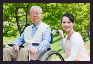 asian caregiver and elderly in a wheelchair - home care image