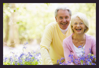 laughing elderly couple in a flower garden - home care image